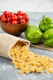 Surowe makarony w rustykalnej torebce z pomidorkami koktajlowymi i papryką na marmurowym stole.