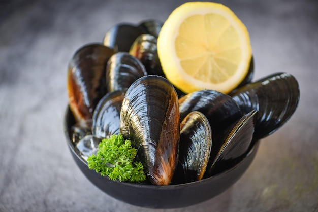 Surowe małże z ziołami cytrynowymi na misce i ciemne. świeży owoce morza skorupiak na lodzie w restauraci