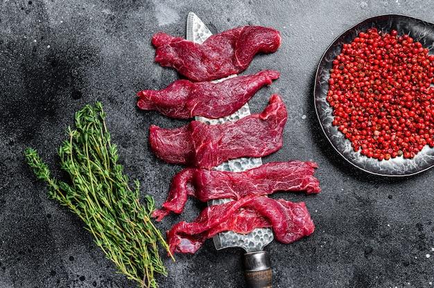 Surowe marmurkowe mięso pokrojone w cienkie paski na beefstroganoff. czarne tło. widok z góry.