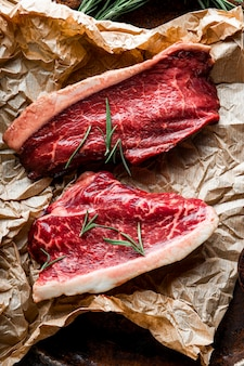 Surowe marmurkowe steki wołowe i przyprawy do ich przygotowania na starym drewnianym tle, widok z góry, pionowe zdjęcie. surowe mięso wołowe na stole w kuchni. zdjęcie wysokiej jakości