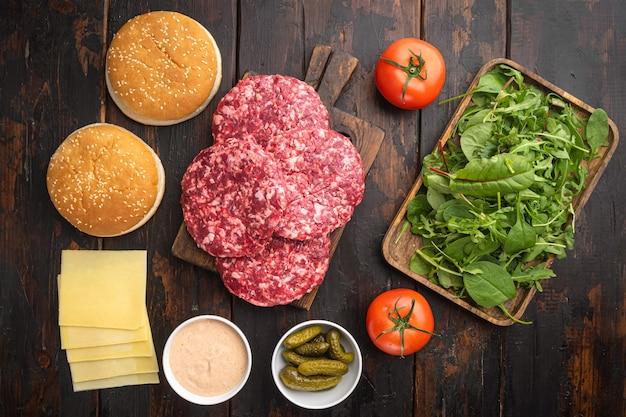 Surowe mielone mięso wołowe kotlety stek z burgerów i przyprawy z zestawem bułek, na starym ciemnym drewnianym stole