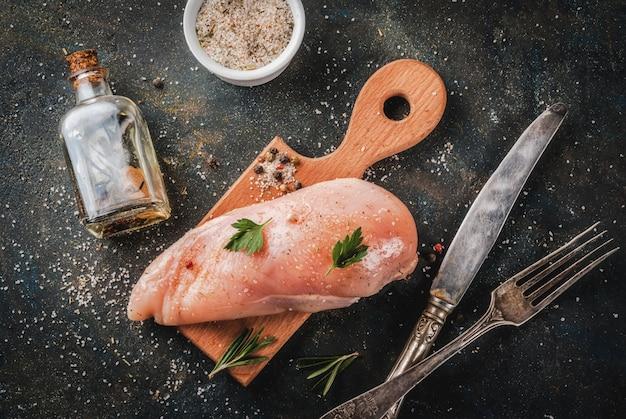 Surowe mięso, filet z piersi kurczaka, z oliwą z oliwek, zioła i przyprawy na ciemnym niebieskim tle widok z góry
