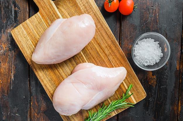 Surowe mięso, gotowe do grilla lub grillowanego fileta z piersi kurczaka, ziołami i przyprawami na ciemnym zardzewiałym tle drewnianych, widok z góry z bliska.