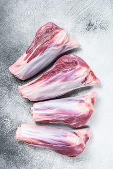 Surowe mięso jagnięce golonki na kamiennym stole. białe tło. widok z góry.