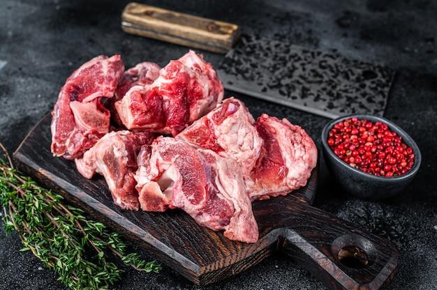 Surowe mięso jagnięce gulasz z kości na drewnianej desce rzeźnika i tasak