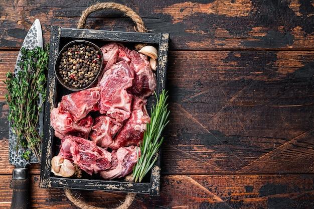 Surowe mięso jagnięce lub kozie pokrojone w kostkę na gulasz z kością. ciemne drewniane tło. widok z góry. skopiuj miejsce.