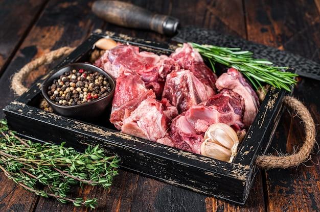Surowe mięso jagnięce lub kozie pokrojone w kostkę na gulasz z kością. ciemne drewniane tło. widok z góry.