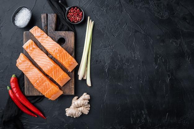 Surowe mięso łososia na kotlety, na czarnym tle z teksturą, widok z góry z miejscem na tekst