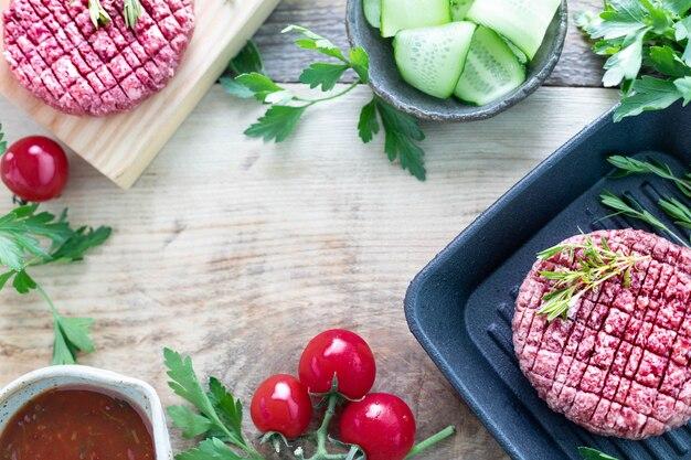 Surowe mięso mielone hamburger z ziołami i przyprawami przygotowane do grillowania. skopiuj widok z góry przestrzeni.