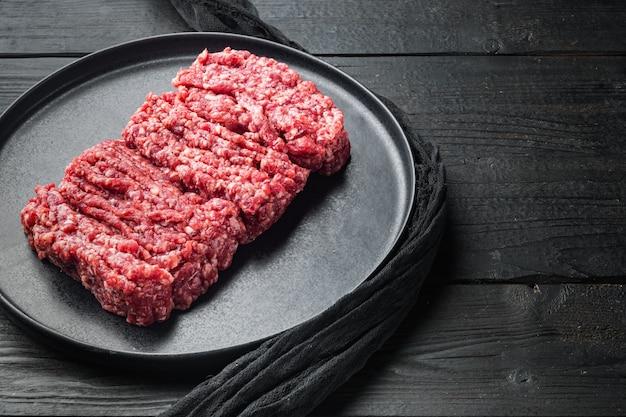 Surowe mięso mielone świeże, na tle czarny drewniany stół z miejsca kopiowania tekstu