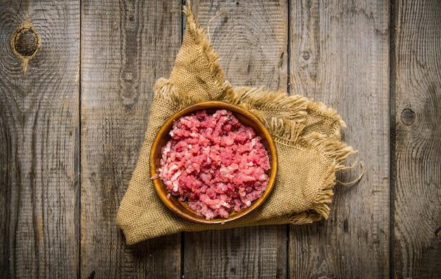 Surowe mięso mielone w drewnianej misce na starej tkaninie