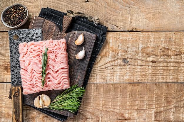 Surowe mięso mielone z kurczaka i indyka na drewnianej desce do krojenia z tasakiem rzeźniczym. drewniane tła. widok z góry. skopiuj miejsce.