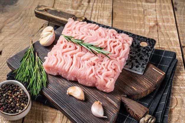 Surowe mięso mielone z kurczaka i indyka na drewnianej desce do krojenia z tasakiem rzeźniczym. drewniane tła. widok z góry.