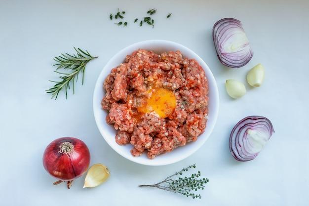 Surowe mięso mielone z pieprzem, jajkiem, ziołami i przyprawami do gotowania kotletów, hamburgerów, klopsików. koncepcja - gotowanie, przepisy kulinarne, pyszne dania.