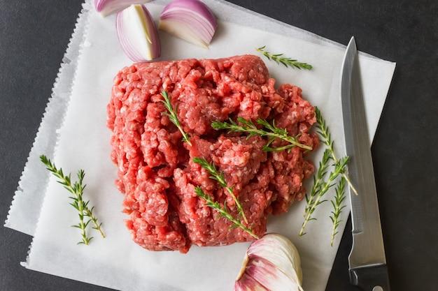 Surowe mięso mielone z tymiankiem i przyprawami do gotowania kotletów, hamburgerów, klopsików.