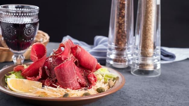Surowe mięso mrożone stroganina z serem, kaparami i cytryną. plasterki mrożonego surowego mięsa na talerzu
