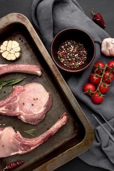 Surowe mięso na patelni i warzywach