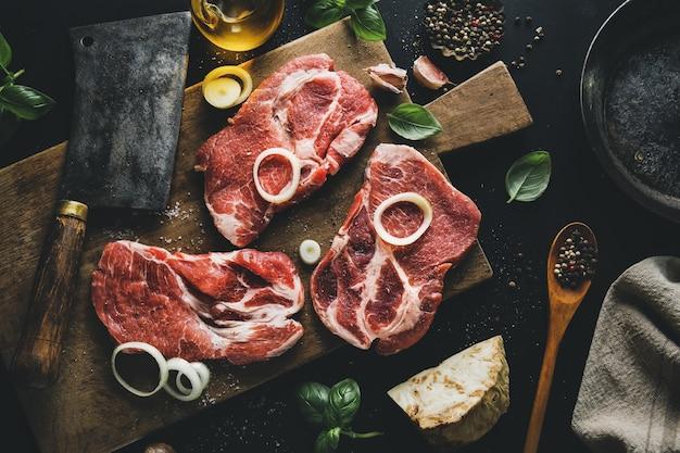 Surowe mięso na pokładzie z przyprawami i ziołami na pokładzie na ciemnej powierzchni