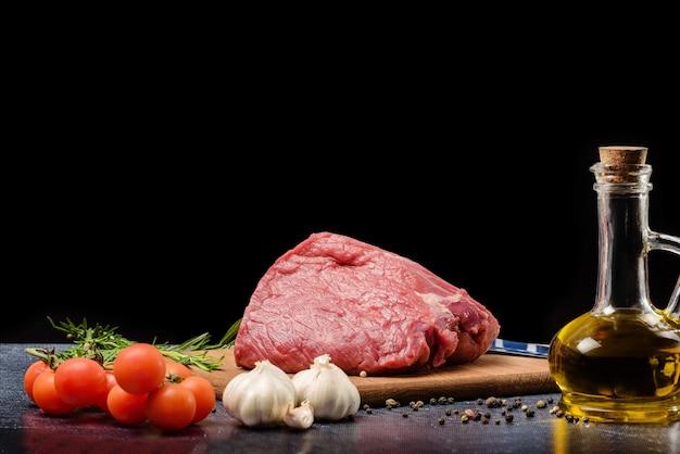 Surowe mięso na stole z przyprawami, odizolowane na czarno