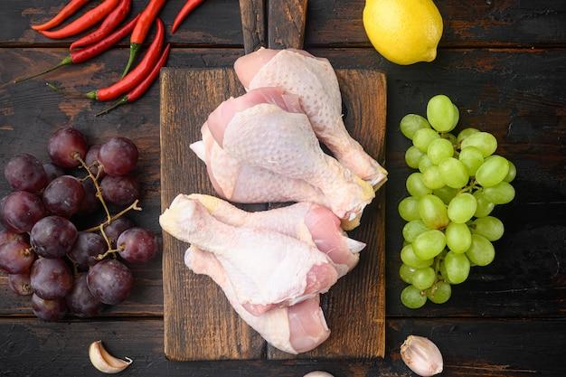 Surowe mięso. nogi kurczaka, kawałki podudzia, na drewnianej desce do krojenia, na starym ciemnym drewnianym stole, widok z góry na płasko