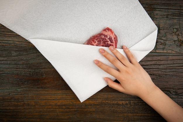 Surowe mięso odsącza się ręcznikiem kuchennym