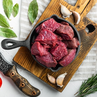 Surowe mięso pokrojone w kostkę na zestaw do duszenia, na żeliwnej patelni, na białej kamiennej powierzchni, widok z góry na płasko, format kwadratowy