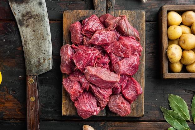 Surowe mięso pokrojone w kostkę na zestaw gulaszowy i ziemniaki, na starym ciemnym drewnianym stole