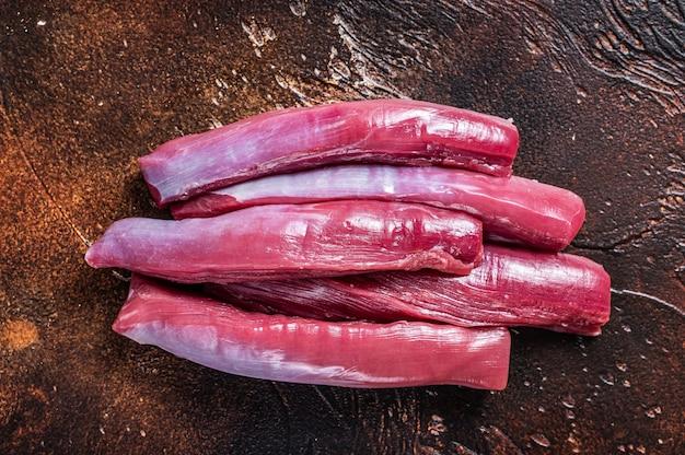 Surowe mięso polędwicy jagnięcej na stole rzeźnika. ciemne tło. widok z góry.