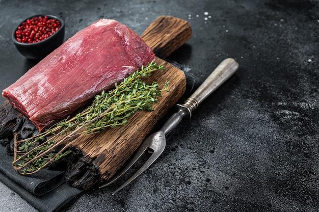 Surowe mięso polędwicy wołowej na desce drewnianej rzeźnika. czarne tło. widok z góry. skopiuj miejsce.