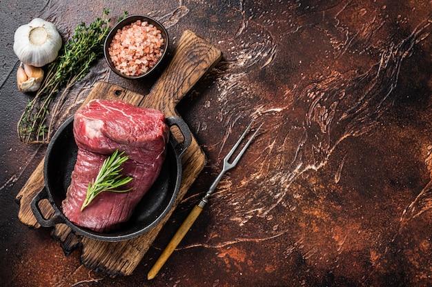 Surowe mięso polędwicy wołowej na patelni z ziołami. ciemne tło. widok z góry. skopiuj miejsce.