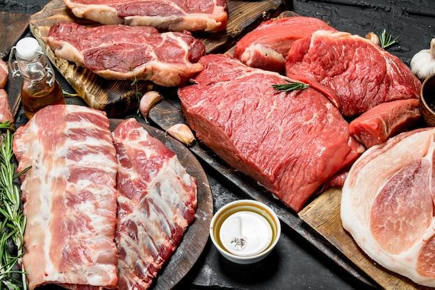 Surowe mięso. różne rodzaje mięsa wieprzowego i wołowego. na czarnym rustykalnym stole.