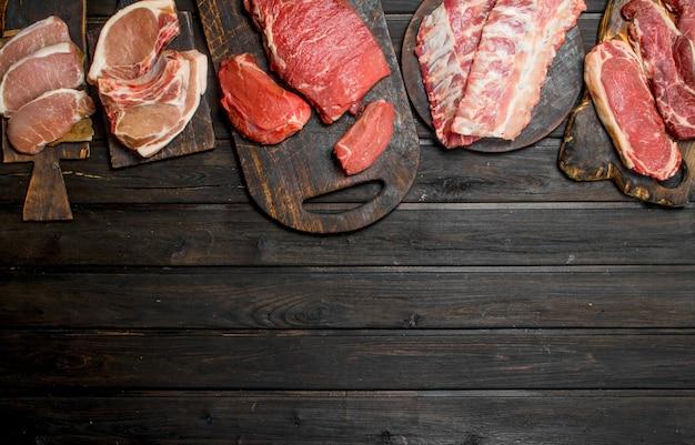 Surowe mięso. różne rodzaje mięsa wieprzowego i wołowego na drewnianym stole.