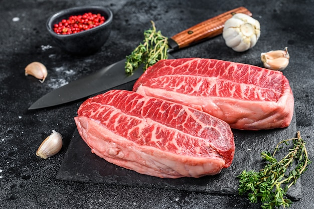 Surowe mięso stek z ostryg twagyu na czarnym ostrzu. widok z góry