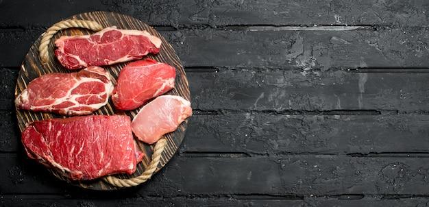 Surowe mięso. steki wołowe i wieprzowe na drewnianej tacy. na czarnym tle rustykalnym.