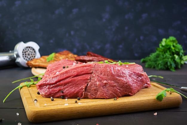 Surowe mięso. świeża wołowina na drewnianym tle