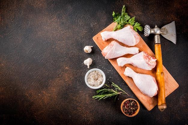 Surowe mięso, udka z kurczaka, z ziół i przypraw n ciemny zardzewiały tło, kopia przestrzeń widok z góry