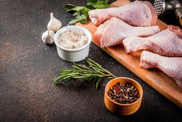 Surowe mięso, udka z kurczaka, z ziół i przypraw n ciemny zardzewiały tło, miejsce