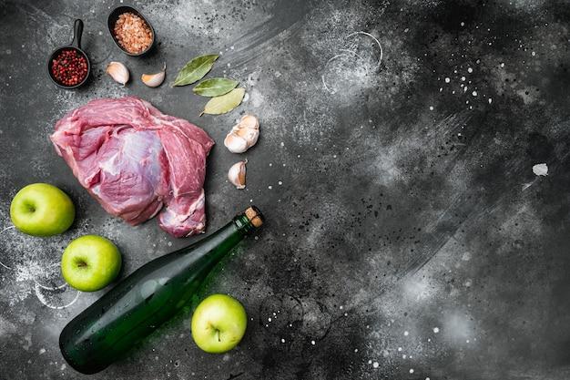 Surowe mięso wieprzowe na drewnianej desce do krojenia przy kuchennym stole do gotowania, z suchym cydrem jabłkowym, na tle czarnego ciemnego kamiennego stołu, widok z góry płasko leżał, z miejscem na tekst