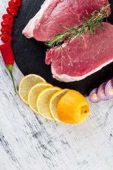 Surowe mięso wieprzowe polędwiczka na czarnym talerzu łupkowym z dodatkiem przypraw - rozmarynu, imbiru, papryczki chilli, cebuli widok z góry. leżał na płasko. skopiuj miejsce.