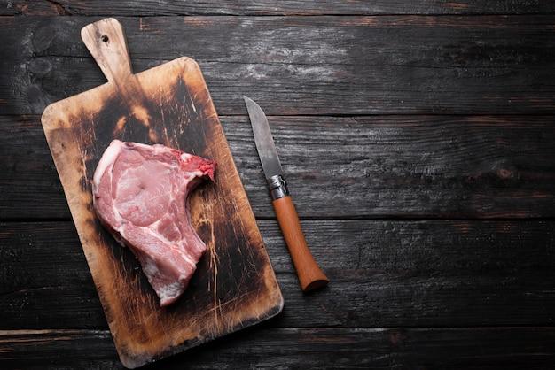 Surowe mięso wieprzowe, świeży kawałek leży na desce do krojenia, stół kuchenny wykonany z drewna.