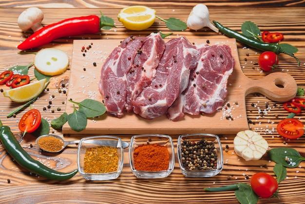 Surowe mięso wieprzowe z przyprawami i warzywami na drewnianym stole