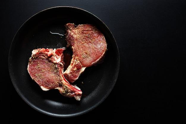 Surowe mięso wieprzowe z przyprawami na patelni