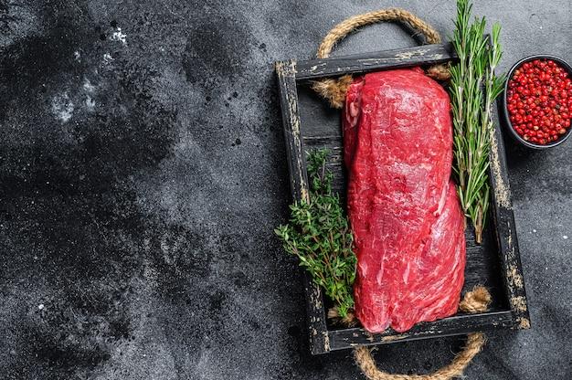 Surowe mięso wołowe całe polędwica na drewnianej tacy z ziołami.