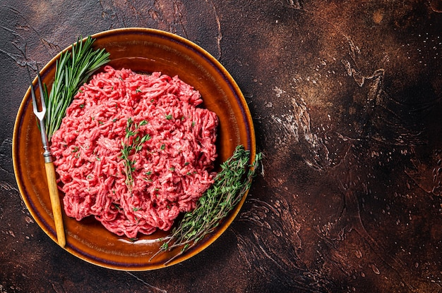 Surowe mięso wołowe i jagnięce mielone na rustykalnym talerzu z ziołami. ciemne tło. widok z góry. skopiuj miejsce.