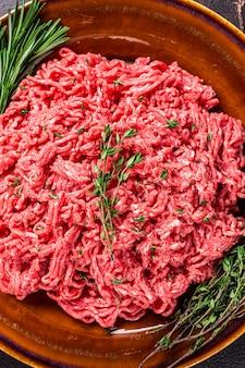 Surowe mięso wołowe i jagnięce mielone na rustykalnym talerzu z ziołami. ciemne tło. widok z góry.