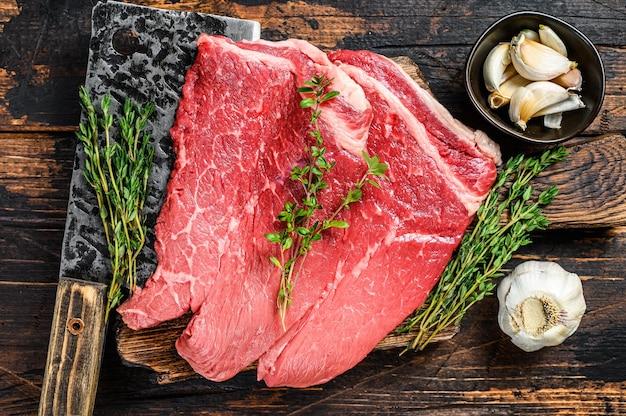 Surowe mięso wołowe kotlet rumsztyk na desce do krojenia. ciemny drewniany stół. widok z góry.
