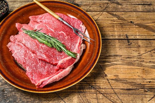 Surowe mięso wołowe kotlet rumsztyk na talerzu. drewniany stół. widok z góry.