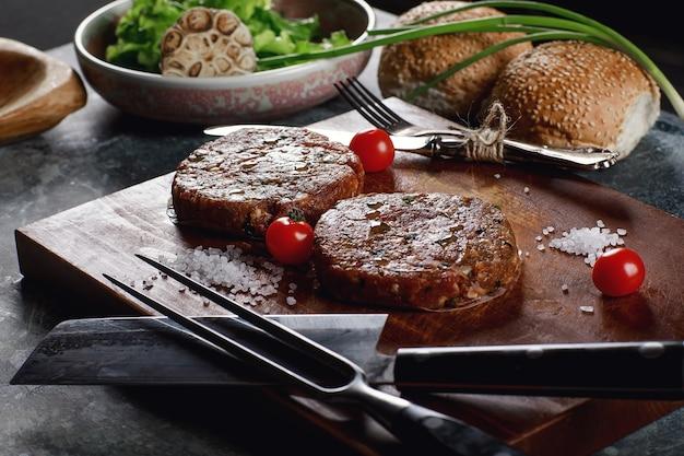 Surowe mięso wołowe mielone burger steak kotlety ze składnikami na pokładzie