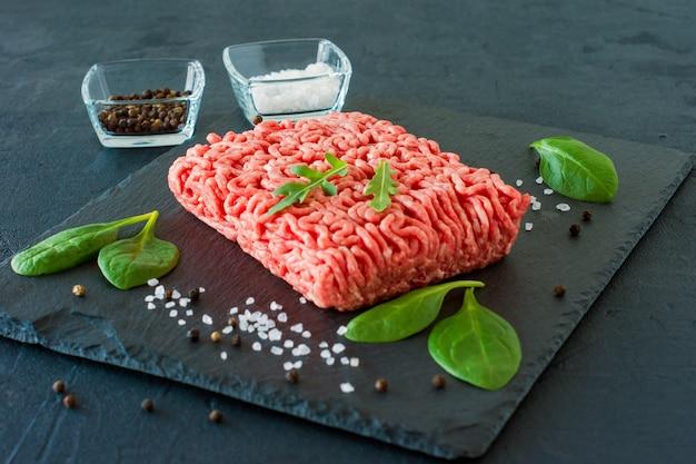 Surowe mięso wołowe mielone na łupku z liśćmi i przyprawami.