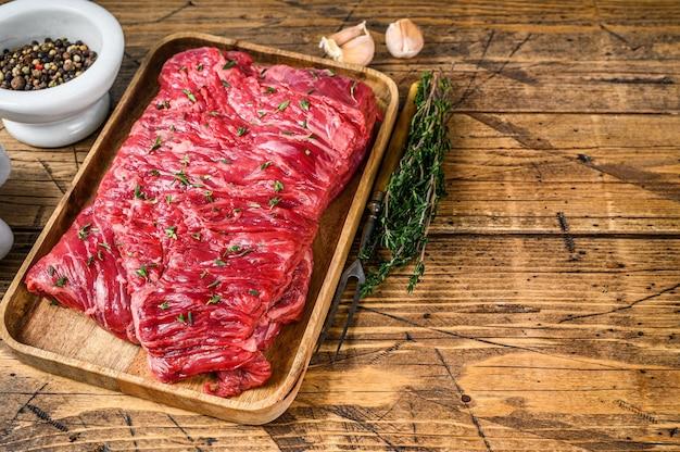 Surowe mięso wołowe okrągłe pokrojone na drewnianej tacy z ziołami. drewniane tła. widok z góry. skopiuj miejsce.